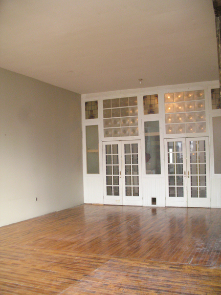 "Photograph highlighting the hardwood floors, 12' 4"" ceilings and the artist designed glass wall of loft 2F at the warehouse in Philadelphia"
