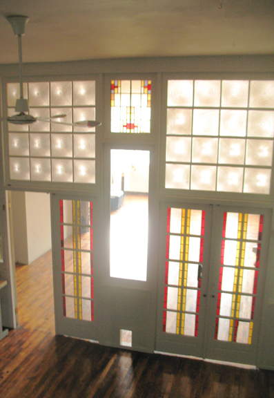 Light shimers through the two sets of stained glass double doors that devide the front and center spaces of loft 2F in this photograph.
