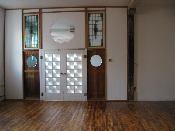 the over size double doors and stained glass windows between the center and rear spaces in the loft are shown in this photograph